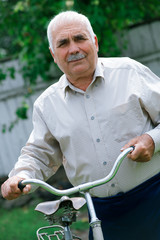 Senior man leaning on the handlebar of his bicycle