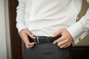 The man corrects a belt.