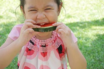 little girl eating juicy watermelon in summertime