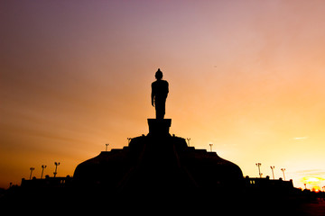 Silhouette of standing Buddha statue at sunset