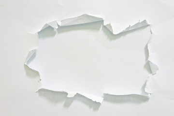 Hole ripped in paper on white background