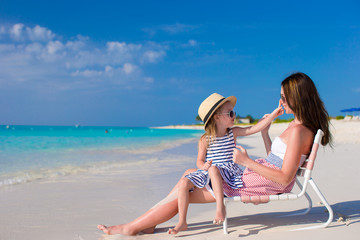 Young mother and adorable little daughter at tropical beach
