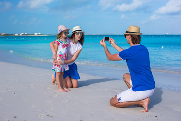 Young father making photo on phone of family at beach