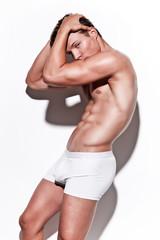 Male muscled underwear model wearing white shorts. Blonde hair.