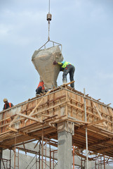 Group of construction workers casting beam