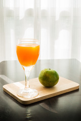 Glass of freshly pressed orange juice with orange