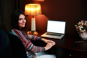 Young smiling woman sitting at the table with laptop at home