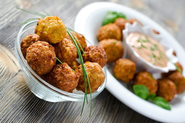 Falafels ready to eat on a plate with sauce and herbs
