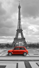 Eiffel tower with car. Black and white photo with red element.