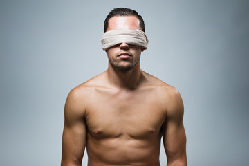 Portrait of young naked blindfold man.