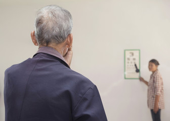 Elderly patient looking at eye chart