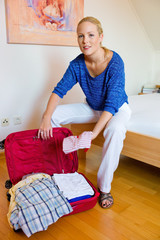 Frau beim Kofferpacken für die Urlaubsreise