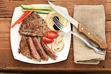 grilled meat on a plate serving rustic wooden background
