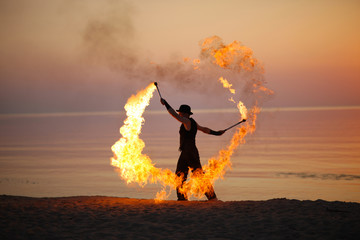 Impressive fire show, torch twirling on the beach