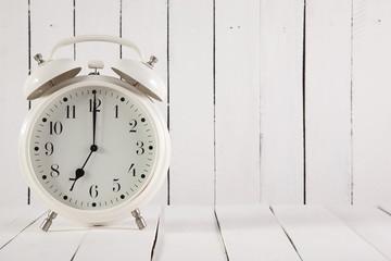retro alarm clock on white wooden background