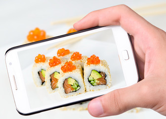 Hands taking photo sushi   with smartphone