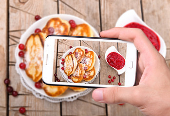 Hands taking photo pancakes with smartphone