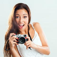 Cute girl holding retro camera.