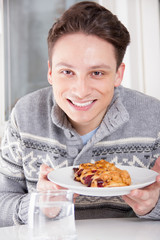 smiling man holding dessert on the plate