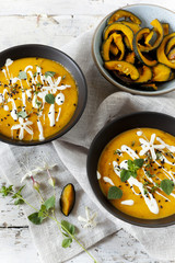 cream of pumpkin and carrot soup on bowls with sour cream
