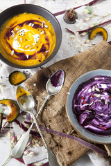 cream of pumpkin and purple carrot soup on bowls with sour cream