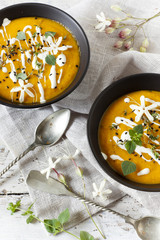 cream of pumpkin and carrot soup on two bowls with sour cream