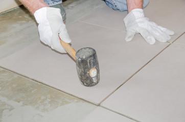 Tiler using a rubber mallet