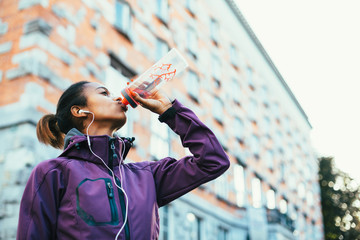 Young woman drinking water after running in city