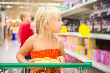 Adorable girl in shopping cart looks at goods on shelves in supe