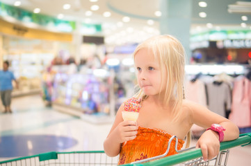 Adorable girl eat fruit ice cream with rainbow sprinkles in shop