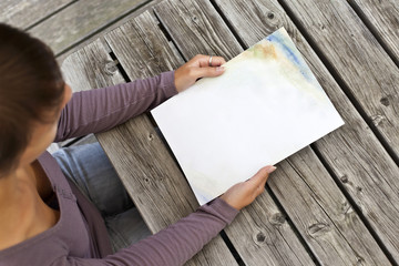 Young woman sitting at table with a booklet with white Cover