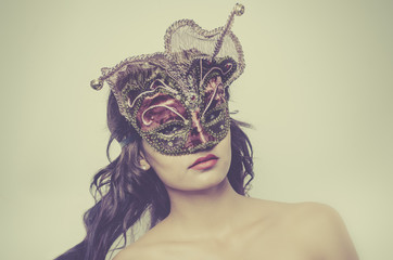Beautiful young woman wearing Venetian mask