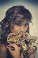 Beautiful young woman wearing Venetian mask