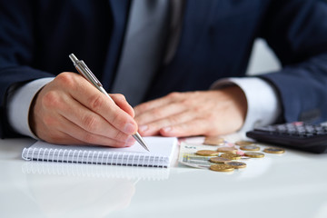 Businessman hand holding a pen writing on notepad