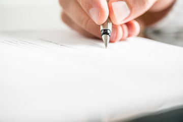 Man writing on a document with a fountain pen
