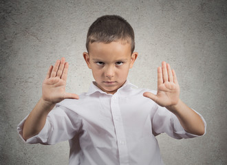 Boy raises arms stop gesture with hands grey wall background