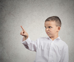 Unhappy boy pointing with finger at copy space, grey wall