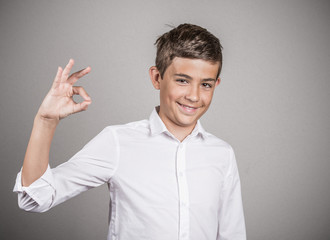 Happy teenager showing Ok sign isolated grey background