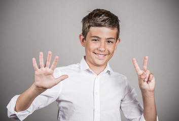 Happy teenager showing seven fingers, number 7 gesture