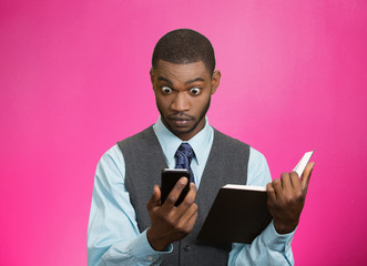 Shoked man with phone holding book reading bad news