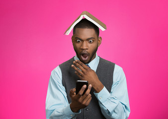 Man holding mobile phone book over head shocked, pink background