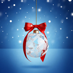 Christmas ball hanging with ribbon on blue background