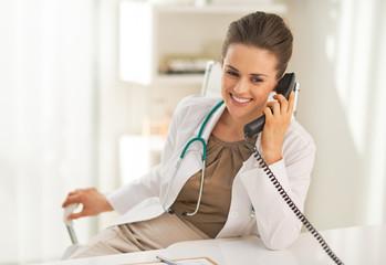 Happy doctor woman talking phone