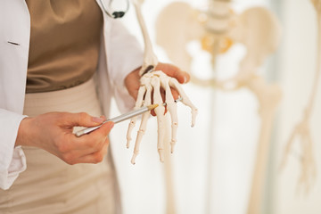 Closeup on doctor woman pointing on hand bone