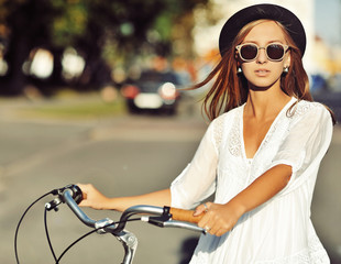 Outdoor fashion portrait of a beautiful blonde with bike