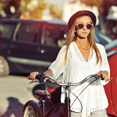 Fashion portrait of beautiful girl with a bicycle