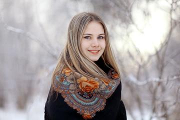 Beautiful Russian woman in a scarf in winter