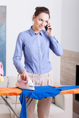 Mother talks on phone while ironing