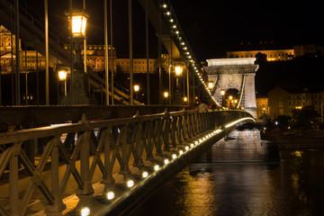Chain bridge Budapest Hungary illuminated at night with old pala