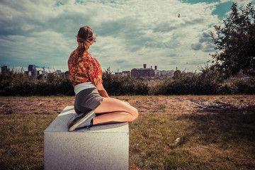 Young woman sitting outside and looking at city